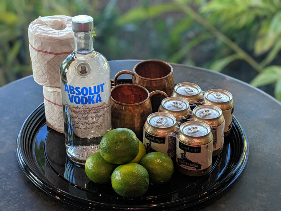 On a tray: Vodka, 6 pack beer, 5 limes, two mule glasses and two roles of toilet paper