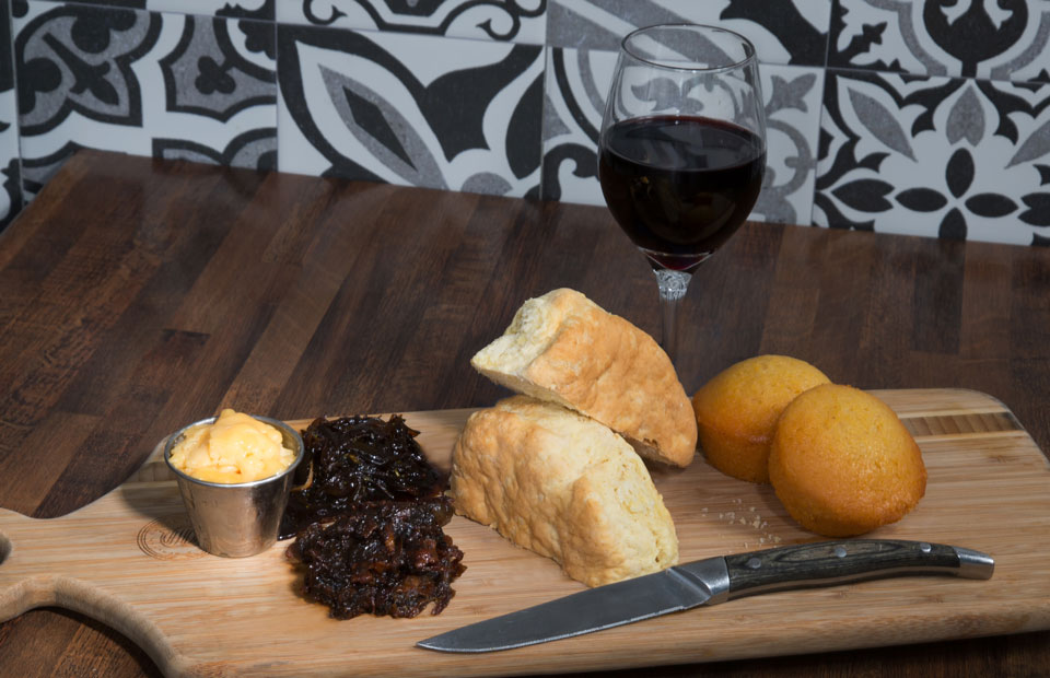 Biscuits, cornbread, marmalade and butter on wooden board